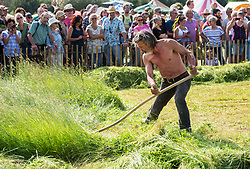 © Licensed to London News Pictures. 10/06/2018. Muchelney, Somerset, UK. SIMON DAMANT, from Cambridgeshire, winner in the finals of the West Country Scythe Championships, at the Green Scythe Fair, held at  Thorney Lakes, Muchelney. The Green Scythe Fair includes the celebrated West Country Scythe Championship, known far and wide for the feats of haymaking by international scythesmen and women. The competition for individuals is based on mowing a 5m x 5m square of grass as quickly as possible, and penalty times are added for an uneven cut or missed areas. Photo credit: Simon Chapman/LNP