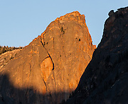 Orange sunset lights a granite peak in the Sawtooth Wilderness (above Redfish Lake Creek), Blaine County, Idaho, USA. The Sawtooth Range (part of the Rocky Mountains) are comprised of the pink granite of the 50 million year old Sawtooth batholith. Sawtooth Wilderness, managed by the US Forest Service within Sawtooth National Recreation Area, has some of the best air quality in the lower 48 states (says the US EPA).
