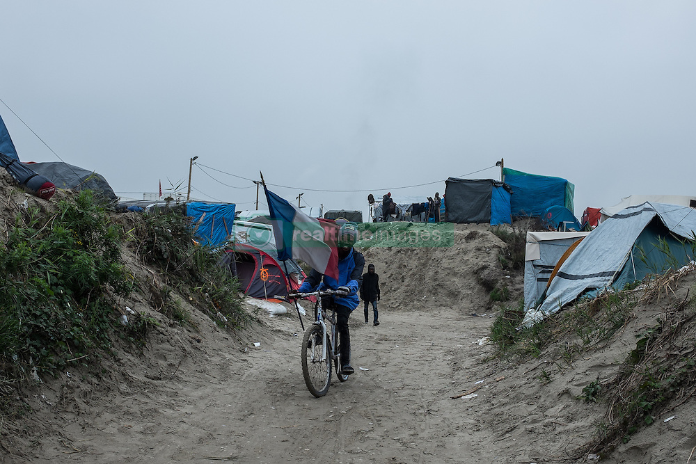 October 24, 2016 - Calais, France - A migrant drives trough the Calais Jungle on a bike with a french flag. After registration, the migrants are distributed on buses. The refugee camp on the coast to the English Channel is to be cleared today. The approximately 8,000 refugees are distributed after the registration by busses to various reception centers in France, on October 24, 2016. (Credit Image: © Markus Heine/NurPhoto via ZUMA Press)