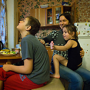 CAPTION: Yana helps her mother pat her brother's back after a piece of apple he's eating goes down the wrong way. The little girl is very good at understanding that Dmitry has particular needs. LOCATION: St Petersburg, Russia. INDIVIDUAL(S) PHOTOGRAPHED: Ksenya Shpunt (mother), Dmitry Shpunt (son) and Yana Shpunt (daughter).