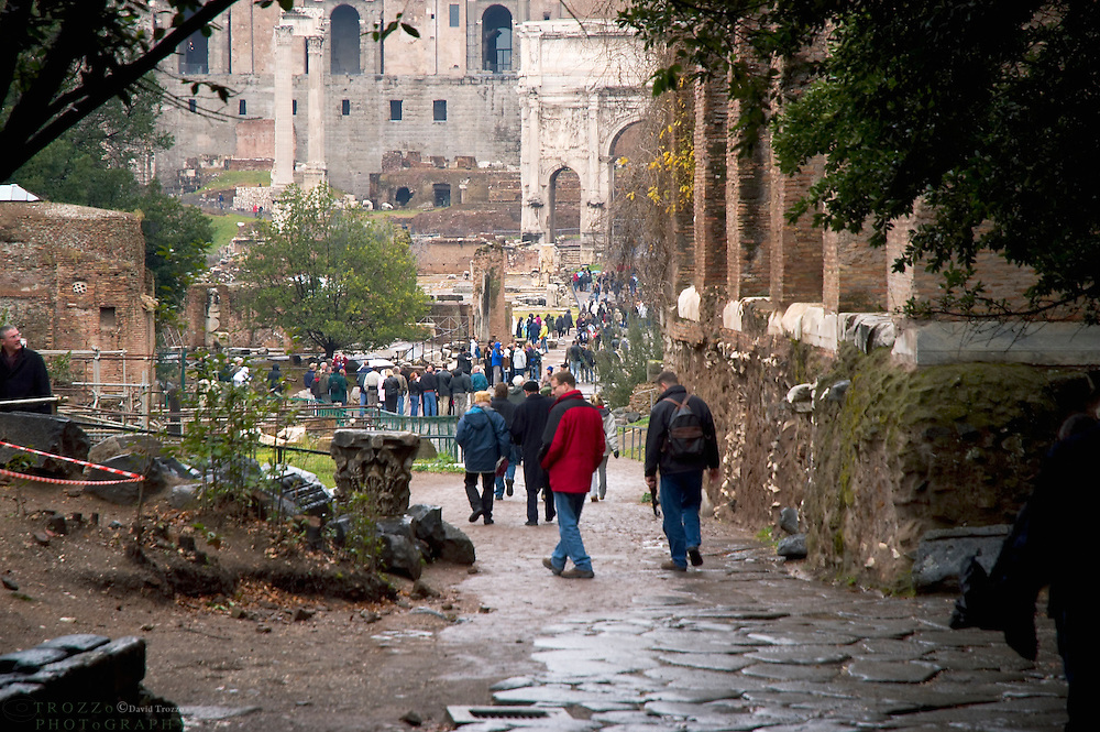 Tourist step back in time as they stroll along in the ancient city of Rome among the ruins of the Roman Forum, antiquity.