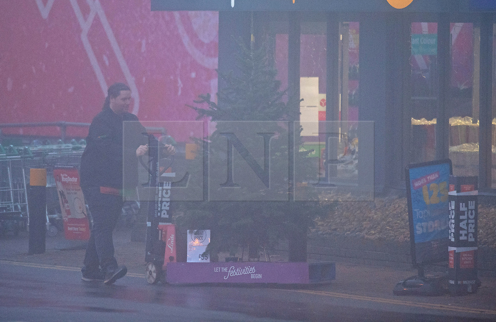 ©Licensed to London News Pictures 30/11/2019.<br /> Orpington,UK.  Homebase worker putting a Christmas tree out front. Freezing foggy conditions this morning across South East London. Freezing cold fog on Sevenoaks Way, Orpington in the London borough of Bromley. Photo credit: Grant Falvey/LNP