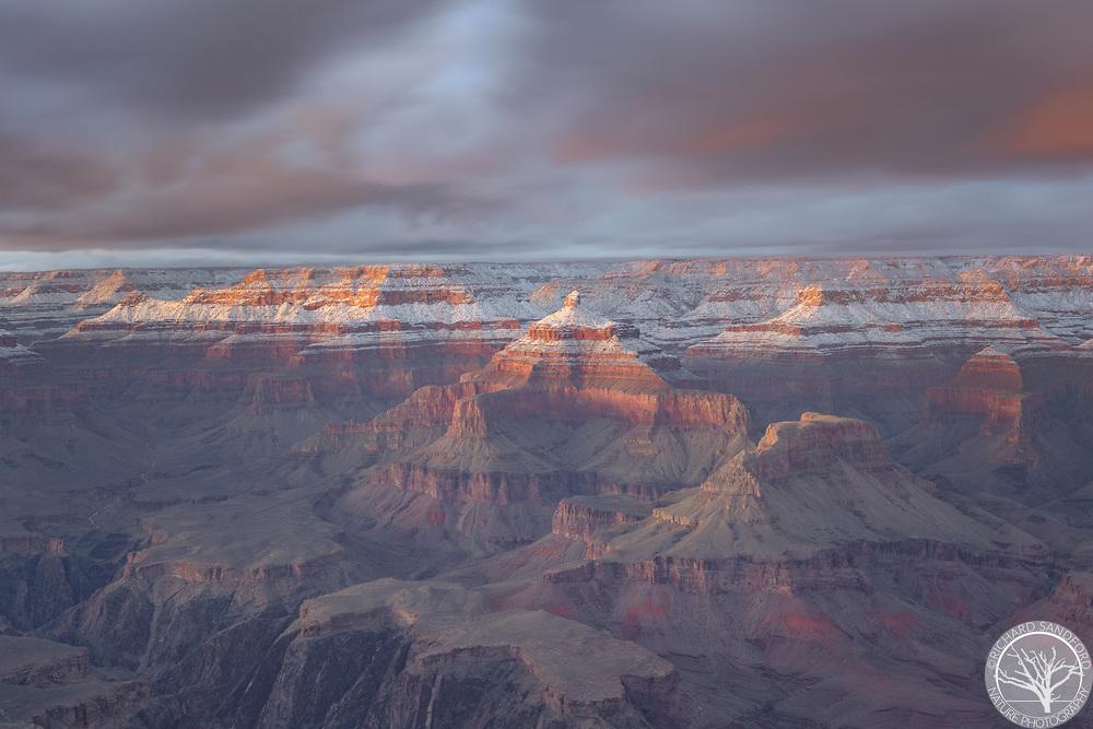 Sunset light on snow covered cliffs of Grand Canyon National Park, AZ