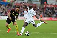 Modou Barrow of Swansea city has a shot at goal as Nicolas Otamendi of Manchester city (l) looks on.  Premier league match, Swansea city v Manchester city at the Liberty Stadium in Swansea, South Wales on Saturday 24th September 2016.<br /> pic by Andrew Orchard, Andrew Orchard sports photography.