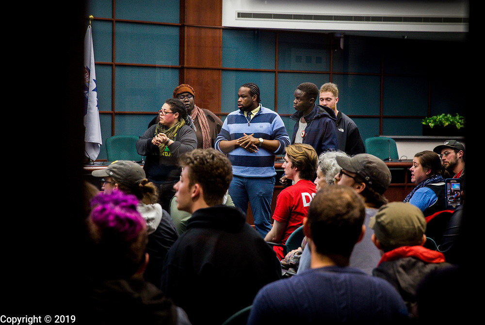 """Protesters """"demand the immediate halt of the BearCat Purchase,"""" after marching to a city council meeting, March 28, 2018 in Bloomington, Ind. City council members adjourned the meeting after being interrupted by the protesters."""