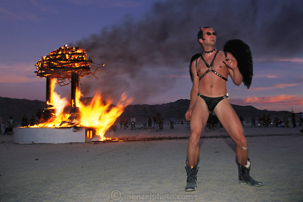 Black Rock Desert, Nevada: Burning Man is a performance art festival known for art, drugs and sex. It takes place annually in the Black Rock Desert near Gerlach, Nevada, USA..Devilish Spokane, Washington chip designer David Wilkins dances as a piece of art burns on the Black Rock Desert/ Burning Man Festival, Nevada.
