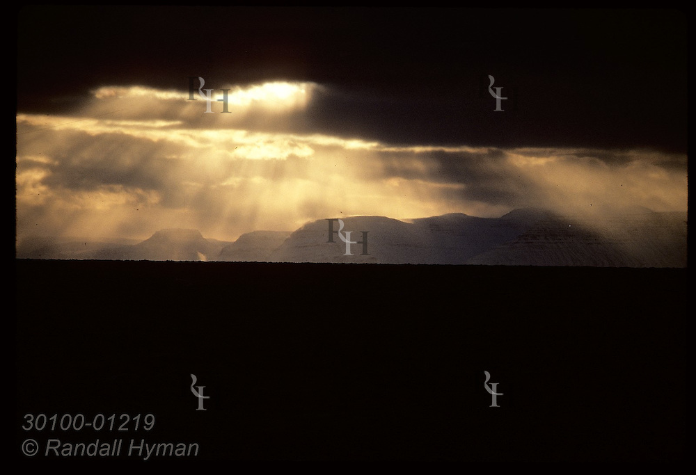 Golden light shimmers upon Hornbjarg cliffs at sunrise as winter storm clears; view from ship. Iceland