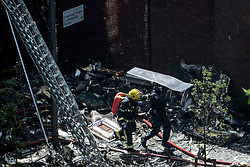© Licensed to London News Pictures. 14/06/2017. London, UK. olice officers with riot shields escort Firemen underneath shields to protect them from falling debris at the scene of a huge fire at the Grenfell tower block in west London. The blaze engulfed the 27-storey building with hundreds of firefighters attending the scene. There are reports of people trapped in the building and multiple fatalities. Photo credit: Ben Cawthra/LNP