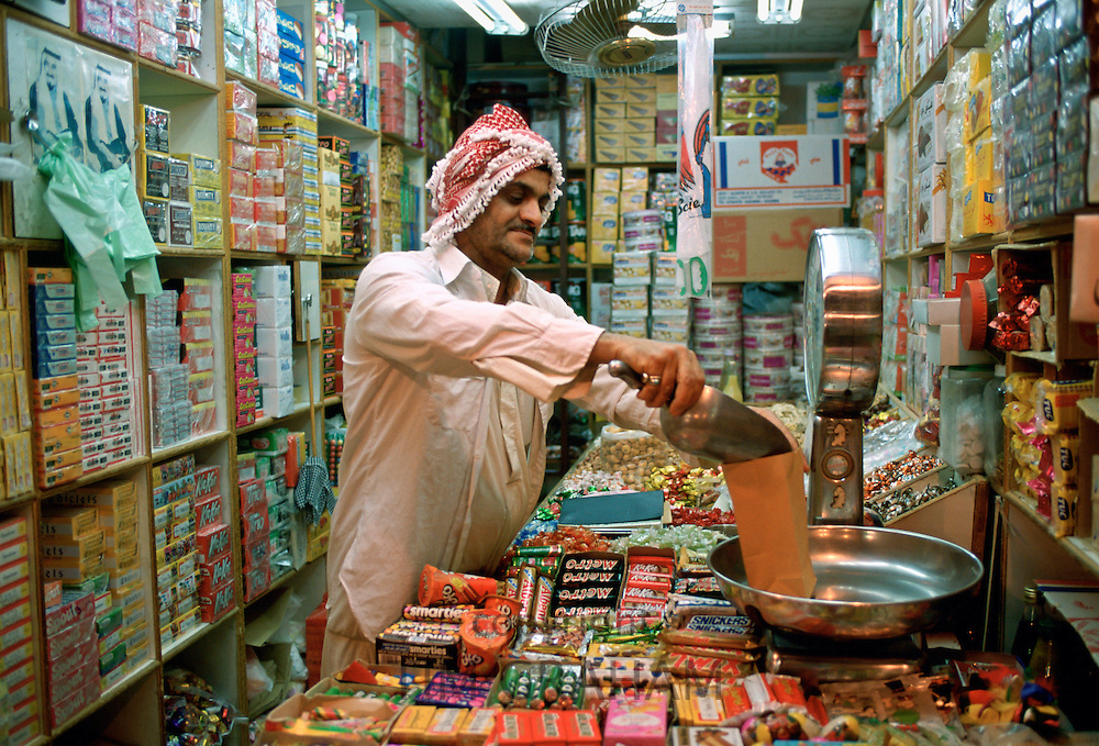A shopkeeper in a sweet and grocery store in Kuwait City in Kuwait weighing sweets for a customer.