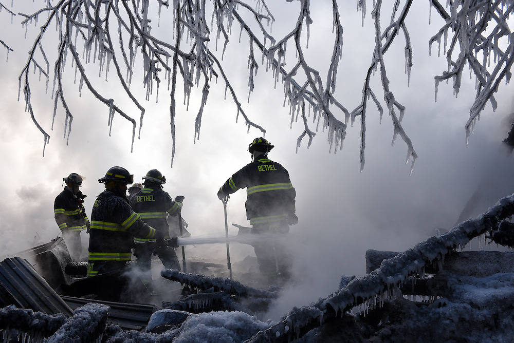 Bethel firefighters work to extinguish any remaining embers inside the destroyed home of Arlene St. Pierre in Bethel Vermont, Friday, Feb. 13, 2015. Bethel, Randolph, Randolph Center and Barnard fire departments responded to the scene at about 8 a.m. Friday when the house and barn were already engulfed in flames. (Valley News - James M. Patterson)<br /> Copyright © Valley News. May not be reprinted or used online without permission. Send requests to permission@vnews.com.