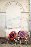 several No Parking traffic sign plates stored against an old wall