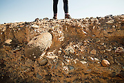 A girl stands on the edge of an eroding mesa bluff, with stones and soil exposed, in the badlands of Utah.