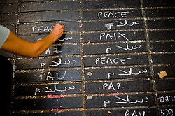 August 21, 2017 - Barcelona, Catalonia, Spain - A woman writtes in several languages the word 'peace' on the floor of Las Ramblas in Barcelona  the same day that Younes Abouyaaqoub, identified as driver of van that sped down Las Ramblas on Thursday, has been shot dead by Catalan police officers in the village of Subirats. (Credit Image: © Jordi Boixareu via ZUMA Wire)