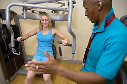Trainer showing woman how to use Multigym weights at Southglade Leisure Centre; Nottingham