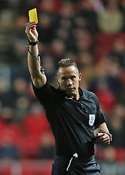 Referee Stephen Martin shows a yellow card