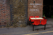 Red seating outside a burger bar under railway arches in the south London borough of Lambeth. The lunch business is now quiet after a period of good business when local workers come to eat and relax during the working day - including staff from a nearby police department. The red seats are the only colourful aspect of this urban landscape.