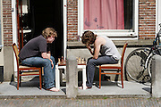 Twee jongens zijn voor hun deur in Utrecht aan het schaken.<br />