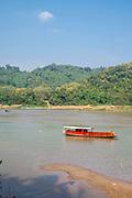 A boat plies the waters of the Mekong River, Luang Prabang, Laos.