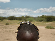 Kapala hunting bird and using the peeping chick on his head to attract the mother and hunt her. At the Hadza camp of Dedauko.