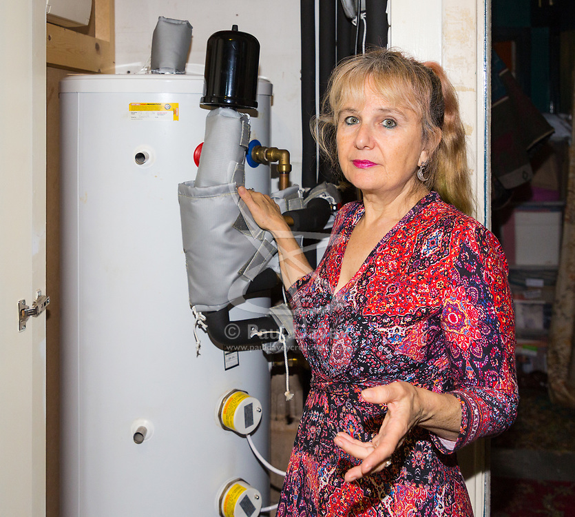 Artist Michelle Baharier, 55, shows how the huge boiler and tank takes up so much space and can cause her flat's temperature to rise above 40º. She is fighting Southwark Council the freeholders of her 2 bedroom Camberwell flat, which she purchased in 2008 under the Right to Buy Scheme. London, November 16 2018.