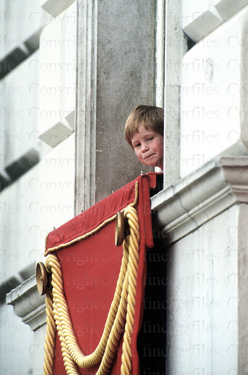 Prince Harry peeps out of the window at Horseguards Parade, London to watch the Trooping of the Colour Ceremony in June 1989.