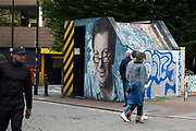 Street art graffiti of local hero and music industry legend Tony Wilson in Manchester, England, United Kingdom. Manchester is a major city in the northwest of England with an industrial heritage. Tony Wilson was an English record label owner, radio and television presenter, nightclub manager, impresario and journalist for Granada Television and the BBC. Wilson was the man behind some of Manchesters most successful bands.