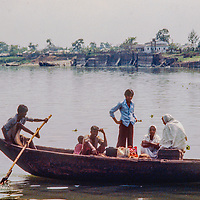 Young ferrymen paddle passengers in crowded boats across a river near Dhaka, Bangladesh.