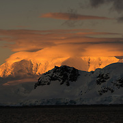 The setting sun casts a beautiful orange glow on clouds and mountains of the dramatic Antarctic landscape of Paradise Harbor, Antarctica.