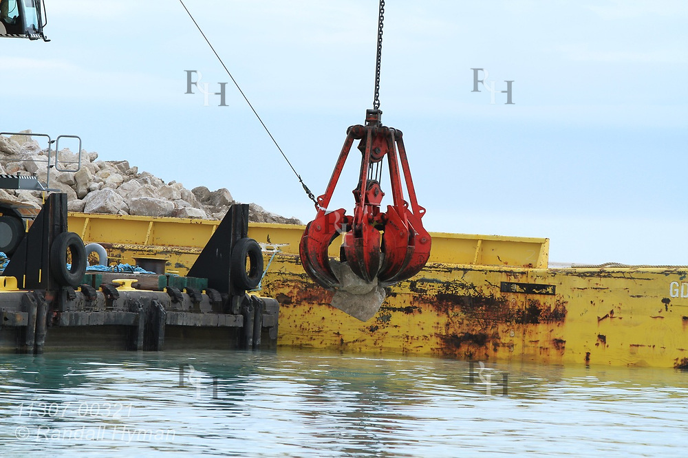 Army Corps of Engineers uses crane and barge to construct underwater rubble ridge designed to disrupt wave energy and reduce shoreline erosion and habitat loss at Illinois Beach State Park; Zion, Illinois.