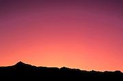 Pink dawn light over silhouette of the Badlands, Badlands National Park, South Dakota