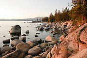 The rocks at Secret Cove have a golden sunlight as the sun sets on Lake Tahoe.
