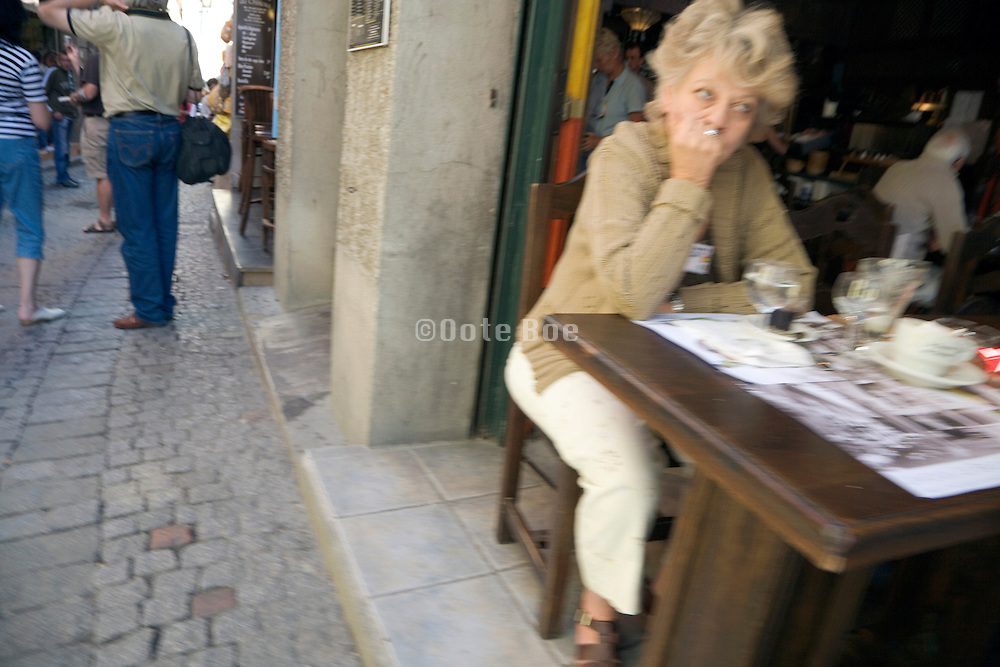 middle aged woman sitting at a restaurant waiting