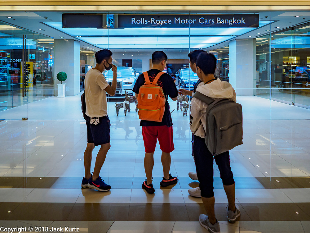 17 DECEMBER 2018 - BANGKOK, THAILAND: Young men look at the Rolls-Royce showroom in Siam Paragon, an exclusive mall in central Bangkok. According to Credit Suisse Global Wealth Databook 2018, which surveyed 40 countries, Thailand has the highest rate of income inequality in the world. In 2016, Thailand was third, behind Russia and India. In 2016, the 1% richest Thais (about 500,000 people) owned 58.0% of the Thailand's wealth. In 2018, they controlled 66.9%. In Russia, those numbers went from 78% in 2016, down to 57.1% in 2018. The Thai government disagreed with the report and said the report didn't take government anti-poverty programs into account and that Thailand was held to an unfair standard because most of the other countries in the report are developed countries in the Organisation for Economic Co-operation and Development.     PHOTO BY JACK KURTZ