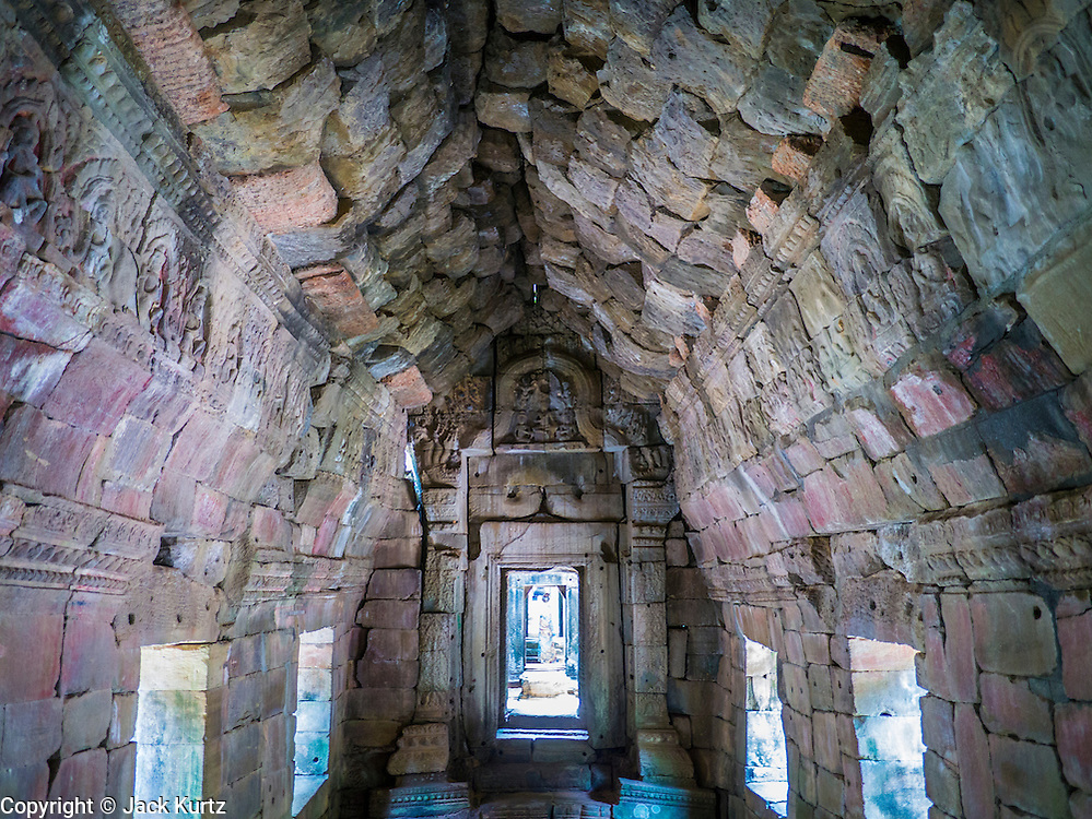 """02 JULY 2013 - ANGKOR WAT, SIEM REAP, SIEM REAP, CAMBODIA:  A stone hallway at Preah Khan, a temple in the Angkor Wat complex. Angkor Wat is the largest temple complex in the world. The temple was built by the Khmer King Suryavarman II in the early 12th century in Yasodharapura (present-day Angkor), the capital of the Khmer Empire, as his state temple and eventual mausoleum. Angkor Wat was dedicated to Vishnu. It is the best-preserved temple at the site, and has remained a religious centre since its foundation– first Hindu, then Buddhist. The temple is at the top of the high classical style of Khmer architecture. It is a symbol of Cambodia, appearing on the national flag, and it is the country's prime attraction for visitors. The temple is admired for the architecture, the extensive bas-reliefs, and for the numerous devatas adorning its walls. The modern name, Angkor Wat, means """"Temple City"""" or """"City of Temples"""" in Khmer; Angkor, meaning """"city"""" or """"capital city"""", is a vernacular form of the word nokor, which comes from the Sanskrit word nagara. Wat is the Khmer word for """"temple grounds"""", derived from the Pali word """"vatta."""" Prior to this time the temple was known as Preah Pisnulok, after the posthumous title of its founder. It is also the name of complex of temples, which includes Bayon and Preah Khan, in the vicinity. It is by far the most visited tourist attraction in Cambodia. More than half of all tourists to Cambodia visit Angkor.         PHOTO BY JACK KURTZ"""