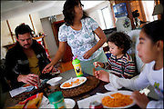 """Lupita Hernandez serves a lunch of spaghetti to her family in their newly purchased trailer home. """"The golden dream is really a house, but this is a place to start,"""" Hernandez said."""
