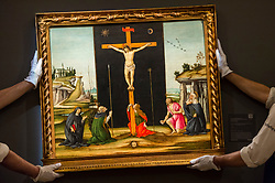 """© Licensed to London News Pictures. 07/12/2020. LONDON, UK. Technicians present """"Christ on the Cross adored by Saints Monica, Augustine, Mary Magdalen, Jerome and Bridget of Sweden"""", by Alessandro di Mariano Filipepi, called Sandro Botticelli (Est. £800k-1.2m). Preview of Sotheby's upcoming Christmas Sale Series of Old Masters and Treasures - paintings and objects spanning 800 Years.  The sales will be at Sotheby's New Bond Street gallery.  Photo credit: Stephen Chung/LNP"""