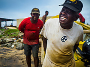 07 OCTOBER 2017 - MORATUWA, SRI LANKA: Fishermen push their boat up the beach in Moratuwa, a fishing village south of Colombo. Fish is an important source for many Sri Lankans.  PHOTO BY JACK KURTZ