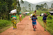 Ayingeneye, far left, Maombi (with a baby), and Mbarabukeye, far right, walk back to their village in Nyanzale, after they were dropped off from a jeep in Mweso, March 14, 2009. These women lived in a faraway village which could take up to five hours on foot. The region was so volatile and rough, the jeep could not access.