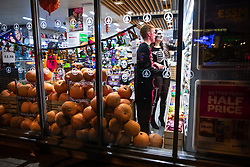© Licensed to London News Pictures . 27/10/2018. Manchester, UK. A man and a woman shop in a convenience shop on Princess Street with its window filled with pumpkins . Revellers on a night out , many in fancy dress , on the weekend before Halloween . Photo credit: Joel Goodman/LNP