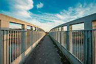 Evening scene in West Sussex near Bury. A metal bridge for walkers across the river Arun.