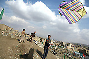Ehsan, 13, the eldest son of Noor Agha, foreground, flies a kite along with other brothers, next to his house, Kabul, Afghanistan, Saturday, March, 10, 2007. Noor Agha is a renowned kite maker who made kites for the movie makers of the best-selling novel, The Kite Runner, which will be distributed by Dreamworks and Paramount Vantage in Nov. this year. Noor Agha's wives, using their special glue, help him produce enough kites to please the clients' needs. Some of his children can also make their own kites with plastic bags and bamboo sticks. As the Afghan New Year's Day (Nawruz) approaching on March 21, the finger tips of Noor Agha's family got busier for mass production.