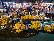 """21 DECEMBER 2015 - BANGKOK, THAILAND: Marigold vendors on the street in Pak Khlong Talat, also called the Flower Market. The market has been a Bangkok landmark for more than 50 years and is the largest wholesale flower market in Bangkok. A recent renovation resulted in many stalls being closed to make room for chain restaurants to attract tourists. Now Bangkok city officials are threatening to evict sidewalk vendors who line the outside of the market. Evicting the sidewalk vendors is a part of a citywide effort to """"clean up"""" Bangkok.       PHOTO BY JACK KURTZ"""