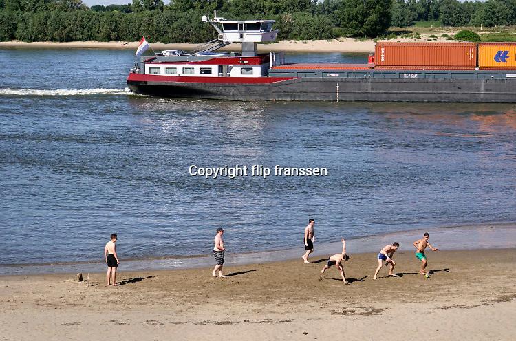 Nederland, Ooij, 21-5-2020  Terwijl mensen zich vermaken langs het water op een warme hemelvaartsdag vaart een binnenvaartschip beladen met containers voorbij . Langzaam daalt het peil van het water in de rivier. In de herfst van 2018 stond de stand bij Lobith op 6,55 meter boven nap . Die is nu nog 8,13 meter, dus nog ruim anderhalve meter hoger .Foto: Flip Franssen