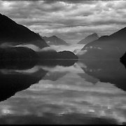 Reflections of solitude in the tranquil Doubtful Sound....You would be forgiven for thinking you'd just stepped out of a time machine while travelling around the South Island of New Zealand... From the misty shades of grey in the fiord of Doubtful Sound, to the fully operational Steamboat the TSS Earnslaw; the Lady of the Lake on Lake Wakitepo, this beautiful island is a Tardis for tourists!..The South Island of New Zealand is roughly the size of England, but it's population of less than a million people means much of the land remains free from human development. It's breathtaking views, and it's climate, could be likened to a cross between Scotland and Scandinavia, and around every corner is mostly unspoilt natural beauty....The Commercialised resort town of Queenstown is the nerve centre of the islands tourism industry, providing the more adventurous thrill seeker with jet boating, skydiving, bungy jumping, and paragliding to name just a few of the more adventurous activities..Queenstown also provides numerous Lord of the Rings tours into middle earth.. In stark contrast the TSS Earnslaw, The Vintage Steamship which has graced the waters of Lake Wakatipu since 1912 provides daily voyages to Walters Peak and a step back in time for it's passengers. The voyage even includes a good old fashion sing-a-long to songs of yesteryear...Just forty five minutes out of Queenstown the Kingston Flyer, a vintage steam train still operates on 14km of track using two AB Pacific Class steam locomotives built in 1925 and 1927 respectively, although the Flyer's history began much earlier in 1878 when it operated between the main south line and Gore..Fijordland on the south Western side of the Island has some of the world's greatest treks; indeed the Milford Track is often booked up way in advance...