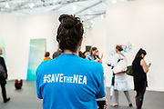 """New York, NY - 5 May 2017. The opening day of the Frieze Art Fair, showcasing modern and contemporary art presented by galleries from around the world, on Randall's Island in New York City. A woman wears a T-shirt captioned """"#SAVEtheNEA,"""" as part of a movement to fight cuts in funding for the National Endowment for the Arts."""