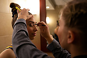Lauren Farley of the Michigan Wolverines puts makeup on Natalie Wojcik before their home exhibition quad meet in the locker room at the Crisler Center on December 18, 2018 in Ann Arbor, Michigan.