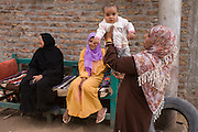 A local family enjoy their youngest child in Bairat, a village on the West Bank of Luxor, Nile Valley, Egypt.