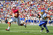 Stanford quaterback Andrew Luck (12) escapes  Derek Muaava's (34) tackle in the 2011 season opener at Stanford University, Palo Alto, Calif, Sept. 3, 2011.  Stanford beat San Jose State 57-3. (Spartan Daily/Stan Olszewski)