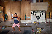Carisma, a young girl practicing weightlifting after school.   Nauru's Weightlifting Gym in Aiwo District (Aiwo's Boys Gym). Girls and boys train here every day starting at 5pm. Nauru's weightlifting champions (including the President of Nauru) have won several gold medals at the Commonwealth Games. Weightlifting is the pride of the nation..Although Nauru is the world's fattest country, with 94% of its population being overweight, teenagers are very fit and sportive. Amongst the favorite sports are weightlifting, Aussie Rule football (a kind of Rugby) and boxing. ..Nauru, officially the Republic of Nauru is an island nation in Micronesia in the South Pacific.  Nauru was declared independent in 1968 and it is the world's smallest independent republic, covering just 21square kilometers..Nauru is a phosphate rock island and its economy depends almost entirely on the phosphate deposits that originate from the droppings of sea birds. Following its exploitation it briefly boasted the highest per-capita income enjoyed by any sovereign state in the world during the late 1960s and early 1970s..In the 1990s, when the phosphate reserves were partly exhausted