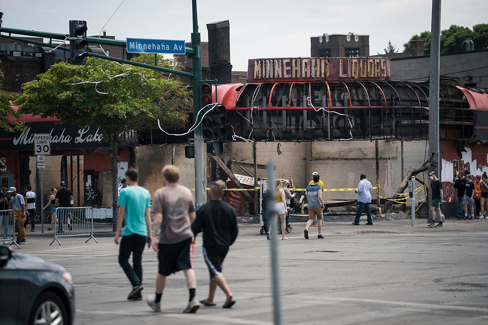 Residents walk past the Minnehaha Liquors store in the Longfellow neighborhood of Minneapolis, Minnesota on Monday, June 1, 2020. The small business was razed to the ground during the civil unrest that overwhelmed the Twin Cities in the final days of May following the death of George Floyd at the hands of Minneapolis Police Department officers.